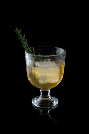 Glass of whiskey and ice with rosemary isolated over black background