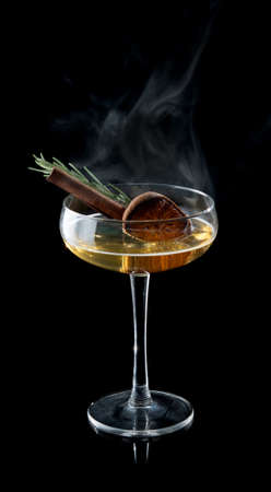 Cocktail and cinnamon syrup with smoke on the black background