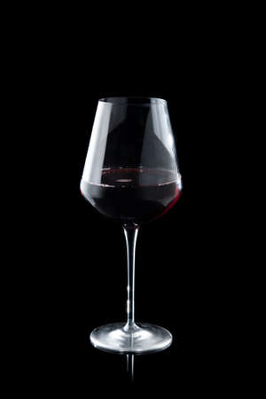 Glass of red wine on the black background