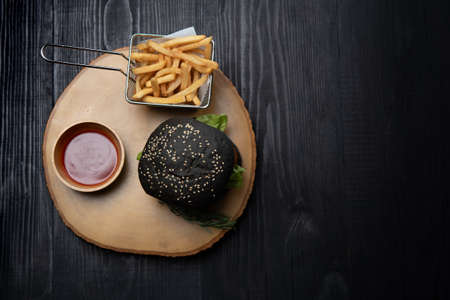 Black burger with french fries on wooden cutting board
