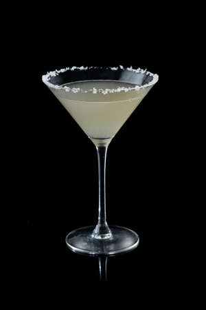 margarita cocktail with salty rim on the black background