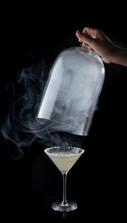 margarita cocktail with salty rim and smoke on the black background