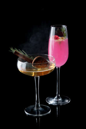 Pink cocktail and cinnamon cocktail on the black background