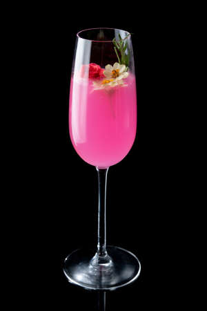 Pink cocktail with flowers on the black background