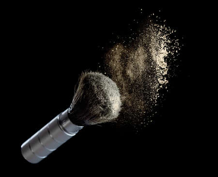 Yellow powder splash and cosmetic brush for makeup on black background