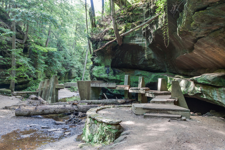 A bridge crossing a creek in Hocking Hills State Park in a valley with evergreen trees and rock overhangs.