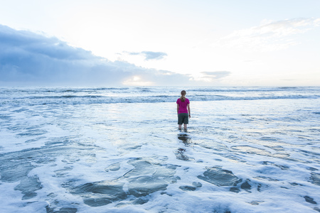 Young lady standing in ocean at the beach wearing shorts and t-shirt, with blonde hair. It is sunrise, and the sun is beginning to come over the horizon.
