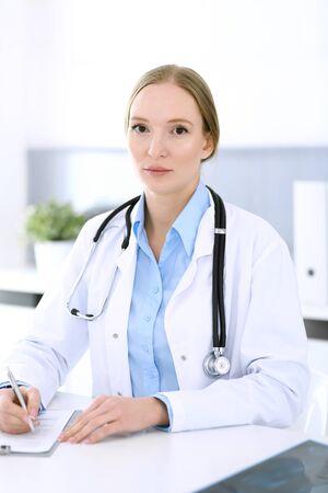 Arztfrau, die Aufzeichnungen über die Medikamentengeschichte ausfüllt, während sie am Schreibtisch im Krankenhausbüro sitzt. Arztfrau bei der Arbeit. Daten in Medizin und Gesundheitswesen