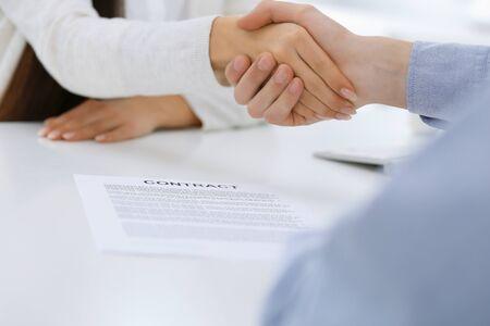 Gli uomini d'affari si stringono la mano durante la riunione o la negoziazione dopo la discussione del contratto. Stretta di mano della donna e dell'uomo d'affari in ufficio mentre è seduto alla scrivania. Concetto di successo
