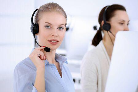 Callcenter-Büro. Schöne blonde Frau, die Computer und Kopfhörer verwendet, um Kunden online zu beraten. Gruppe von Bedienern, die als Kundendienstberuf tätig sind. Geschäftsleute Konzept Standard-Bild