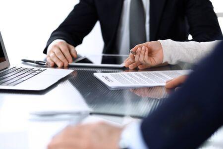 Geschäftsleute diskutieren über Verträge, die bei einem Treffen am Glasschreibtisch im modernen Büro zusammenarbeiten. Unbekannter Geschäftsmann und Frau mit Kollegen oder Anwälten bei Verhandlungen. Teamwork und Partnerschaftskonzept Standard-Bild