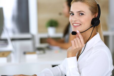 Blonde business woman using headset for communication and consulting people at customer service office. Call center. Group of operators at work at the background