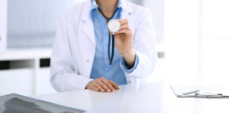 Doctor woman holds stethoscope head close-up. Physician ready to examine and help patient. Medical help and best treatment, medicine concept.