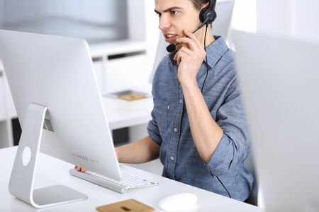 Group of operators at work. Call center. Focus on young man receptionist in headset at customer service. Business concept and casual clothing style