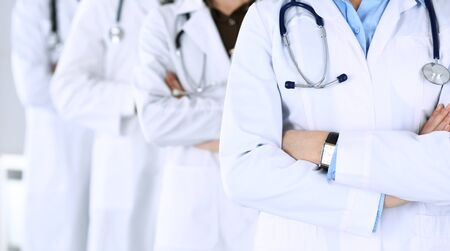 Group of modern doctors standing as a team with arms crossed in hospital office. Physicians ready to examine and help patients. Medical help, insurance in health care, best desease treatment and medic
