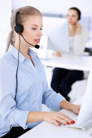 Call center office. Beautiful blonde woman using computer and headset for consulting clients online. Group of operators working as customer service occupation. Business people concept