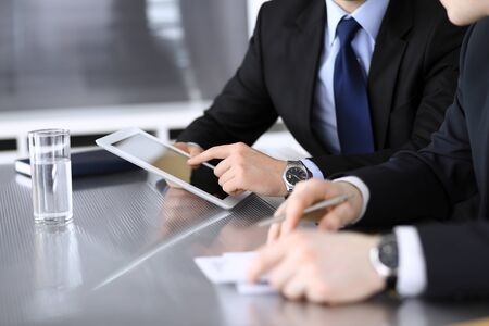 Businessman using tablet computer and work together with his colleague or partner at the glass desk in modern office, close-up. Unknown business people at meeting. Teamwork and partnership concept