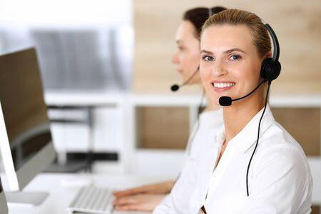Call center. Happy and excited business woman using headset while consulting clients online. Customer service office or telemarketing department. Smiling group of operators at work
