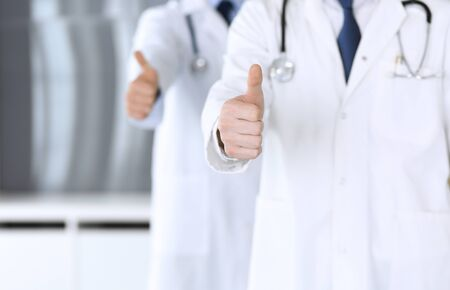 Group of modern doctors standing as a team with thumbs up or Ok sign in hospital office, close-up. Physicians ready to examine and help patients. Medical help, insurance in health care, best treatment 스톡 콘텐츠