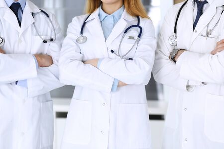 Group of modern doctors standing as a team with arms crossed in hospital office, close-up. Physicians ready to examine and help patients. Medical help, insurance in health care, best treatment and med 스톡 콘텐츠