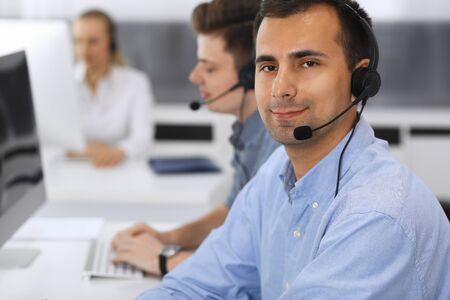 コールセンター。職場でカジュアルな服装のオペレーターのグループ。顧客サービスオフィスでヘッドセットのアダルトビジネスマンに焦点を当てます。ビジネスにおけるテレセールス