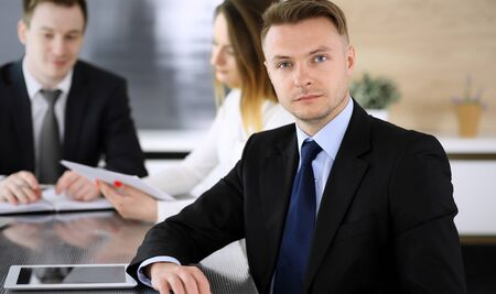 Businessman headshot at meeting in modern office. Unknown entrepreneur sitting with colleagues at the background. Teamwork and partnership concept