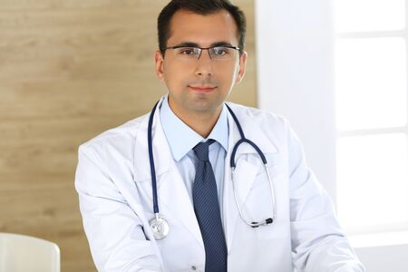 Doctor man typing at laptop computer while sitting at the desk at his working place. Perfect medical service in clinic. Data in medicine and healthcare