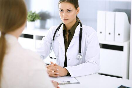 Doctora y paciente sentados y hablando en el examen médico en la oficina del hospital. Blusa de color verde se adapta al terapeuta. Concepto de medicina y salud Foto de archivo