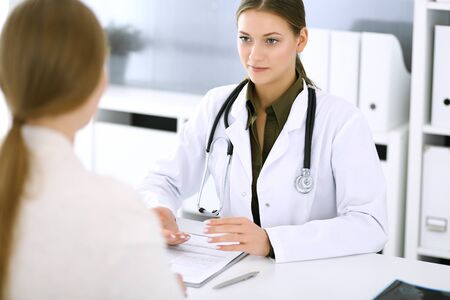 Woman doctor and patient sitting and talking at medical examination at hospital office. Green color blouse suits to therapist. Medicine and healthcare concept