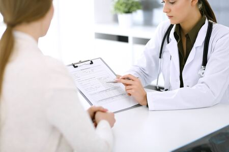 Woman doctor and patient sitting and talking at medical examination at hospital office. Green color blouse suits to therapist. Medicine and healthcare concept Archivio Fotografico