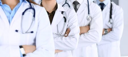 Group of modern doctors standing as a team with arms crossed in hospital office. Physicians ready to examine and help patients. Medical help, insurance in health care, best desease treatment and medicine concept. Stock fotó