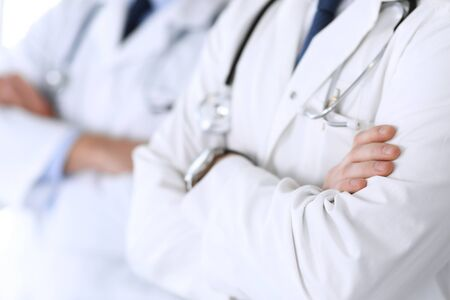 Group of modern doctors standing as a team with arms crossed in hospital office, close-up. Physicians ready to examine and help patients. Medical help, insurance in health care, best treatment and medicine concept.