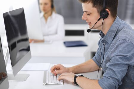 Call center. Group of casual dressed operators at work. Focus on young businessman in headset at customer service office. Telesales in business