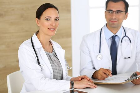 Middle aged woman doctor filling up medical documents or prescription with her male colleague. Group of doctors at work discussing treatment problems while sitting at a desk in hospital. Data in medicine and health care concept