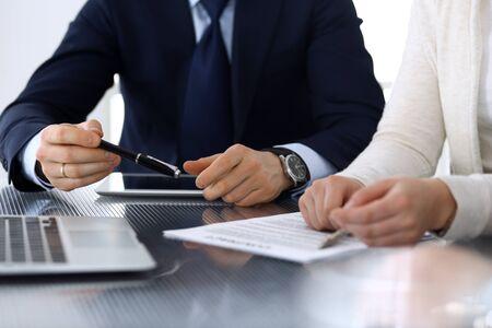 Gens d'affaires discutant du contrat travaillant ensemble lors d'une réunion au bureau en verre dans un bureau moderne. Homme d'affaires et femme inconnus avec des collègues ou des avocats lors de la négociation. Concept de travail d'équipe et de partenariat.