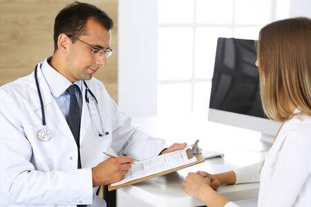 Médico y paciente discutiendo los resultados de un examen físico mientras están sentados en un escritorio en una clínica. Un médico de sexo masculino que usa un portapapeles para completar un historial médico de la medicación de una mujer joven. Conceptos médicos y sanitarios