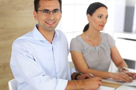 Empresario y empresaria hispana trabajando con computadora en la oficina moderna. Disparo en la cabeza del empresario en la reunión. Grupo de personas diversas. Trabajo en equipo, asociación y concepto empresarial Foto de archivo