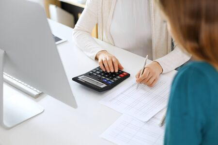 Accountant checking financial statement or counting by calculator income for tax form, hands close-up. Business woman sitting and working with colleague at the desk in office. Audit concept.