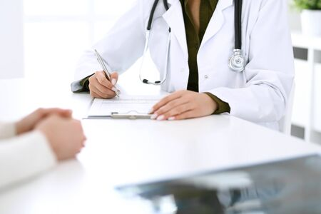 Woman doctor and patient sitting and talking at medical examination at hospital office, close-up. Therapist filling up medication history records. Medicine and healthcare concept. Zdjęcie Seryjne