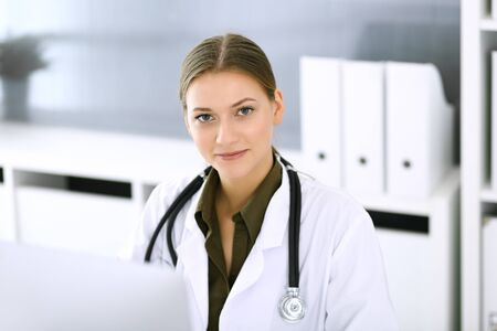 Doctor typing on pc computer while sitting at the desk in hospital office. Physician woman at work. Data in medicine and healthcare