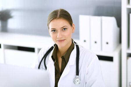 Dokter typt op pc-computer terwijl hij aan de balie in het ziekenhuiskantoor zit. Artsenvrouw op het werk. Gegevens in geneeskunde en gezondheidszorg