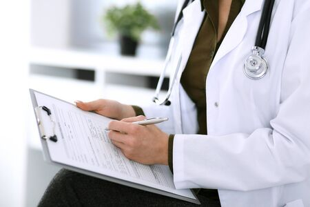 Woman doctor and patient sitting and talking at medical examination at hospital office, close-up. Therapist filling up medication history records. Medicine and healthcare concept Zdjęcie Seryjne
