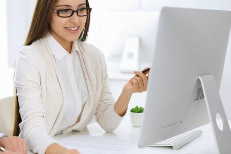 Business woman and man sitting and working with computer and calculator in office. Bookkeeper or accountant checking balance or making finance report. Tax and audit concepts