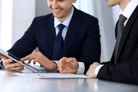 Business people using tablet computer while working together at the desk in modern office. Unknown businessman or male entrepreneur with colleague at workplace. Teamwork and partnership concept Stock fotó
