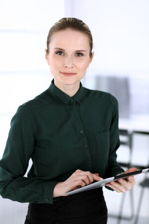 Business woman headshot in modern office. Secretary or female lawyer using tablet computer while standing straight. Business people concept