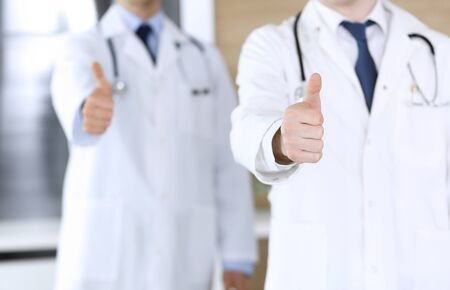 Group of modern doctors standing as a team with thumbs up or Ok sign in hospital office, close-up. Physicians ready to examine and help patients. Medical help, insurance in health care, best treatment and medicine concept. Zdjęcie Seryjne