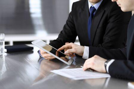 Zakenman met behulp van tablet pc en werk samen met zijn collega of partner aan het glazen bureau in moderne kantoren, close-up. Onbekende zakenmensen tijdens vergadering. Teamwork en partnerschap concept. Stockfoto