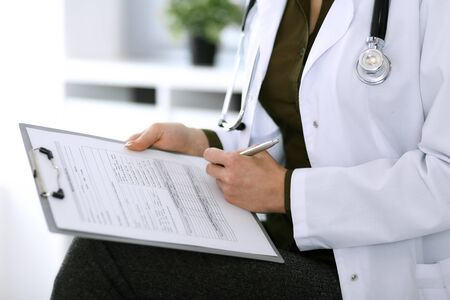 Doctora escribiendo algo en el portapapeles mientras está sentado en la silla, primer plano. Terapeuta en el trabajo llenando registros de historial de medicación. Concepto de medicina y salud Foto de archivo
