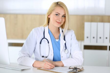 Doctor woman at work while sitting at the desk in hospital or clinic. Blonde cheerful physician filling up medical records form. Data and best service in medicine and healthcare Banco de Imagens