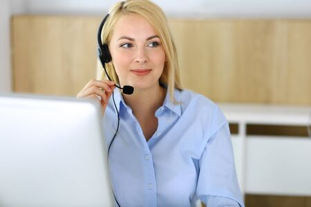 Call center. Blonde business woman sitting in headset at customer service office. Concept of telesales business or home office occupation Banco de Imagens